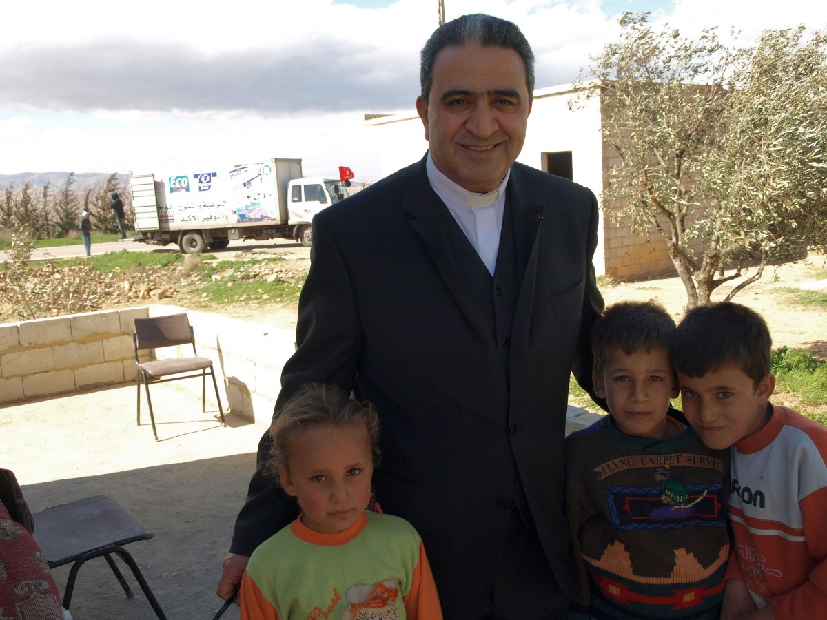 Father Simon Faddoul, president of Caritas Lebanon, with Syrian refugees.
