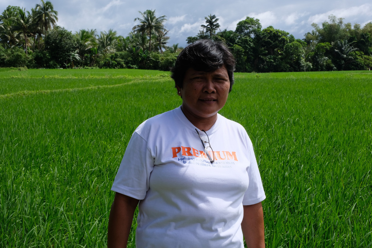 Benilda in front of her rice paddy